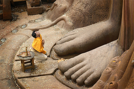 A pilgrim kneels  at the feet of the colossal statue of Bahubali in Shravanabelagola in South India | Photo: Arul Baskaran